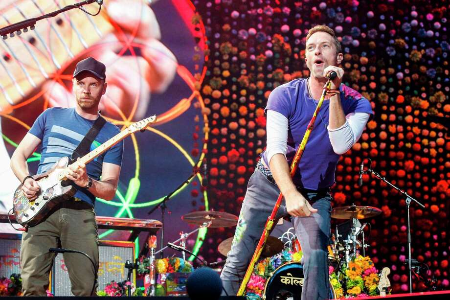 """(FILES) In this file photo taken on July 15, 2017 Lead singer of British band Coldplay Chris Martin (R) with guitarist Jonny Buckland perform at The Stade de France Arena in Saint Denis on the outskirts of Paris. - Coldplay frontman Chris Martin said on November 21, 2019, the band had shelved plans to go on tour to promote their latest album over concerns about the environmental impact of concerts. The band's new album, """"Everyday Life"""", is being released on Friday but its members have decided to play only two gigs, both in the Jordanian capital Amman, which will be broadcast free on YouTube. (Photo by GEOFFROY VAN DER HASSELT / AFP) / RESTRICTED TO EDITORIAL USE (Photo by GEOFFROY VAN DER HASSELT/AFP via Getty Images) Photo: GEOFFROY VAN DER HASSELT, Contributor / AFP Via Getty Images / AFP or licensors"""
