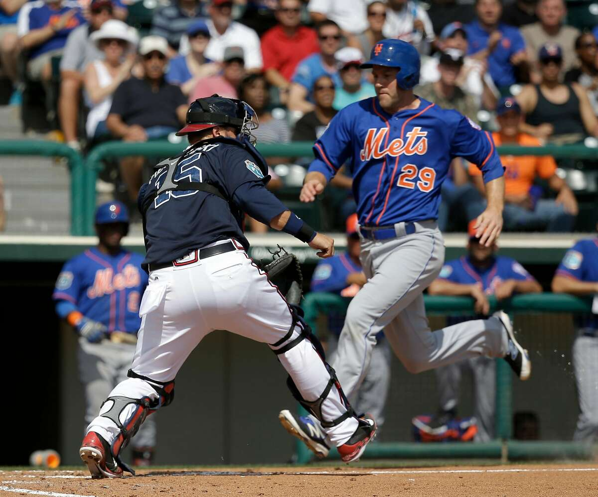 New York Mets' Eric Campbell (29) scores a run as Atlanta Braves catcher A.J. Pierzynski (15) waits for the the throw in the fourth inning of a spring training baseball game, Tuesday, March 8, 2016, in Kissimmee, Fla. (AP Photo/John Raoux)