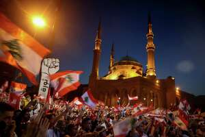 Lebanese anti-government protesters wave the national flag during a demonstration in downtown Beirut this month. The protesters are responding to political and economic uncertainty that has gripped the globe.