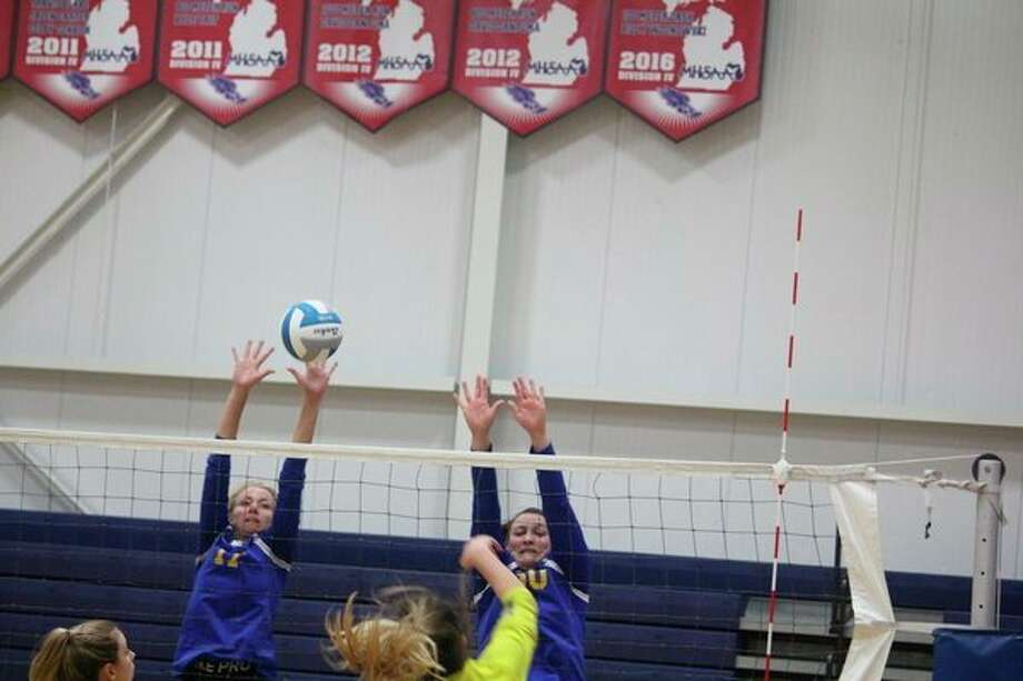 Evart volleyball players Kara Henry (left) and Kelci Elder go after the ball during action this season. (Pioneer file photo)