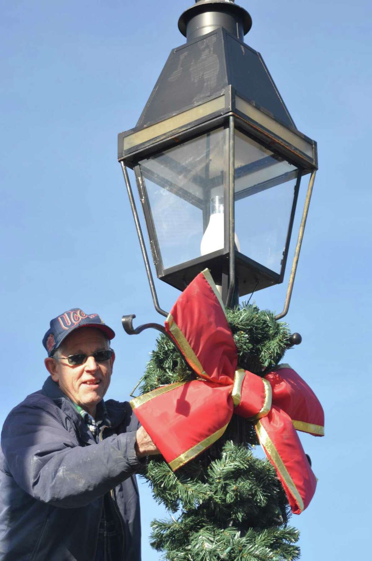 Veteran John Knoche decorated lampposts for the season Saturday, Nov. 23, as a crew of about 25 , half from the American Legion and half from its youth baseball team, decorated 57 village lampposts.