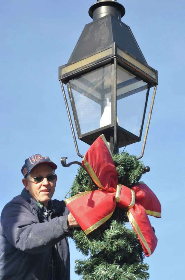 Veteran John Knoche decorated lampposts for the season Saturday, Nov. 23, as a crew of about 25 , half from the American Legion and half from its youth baseball team, decorated 57 village lampposts. Photo: Macklin Reid / Hearst Connecticut Media
