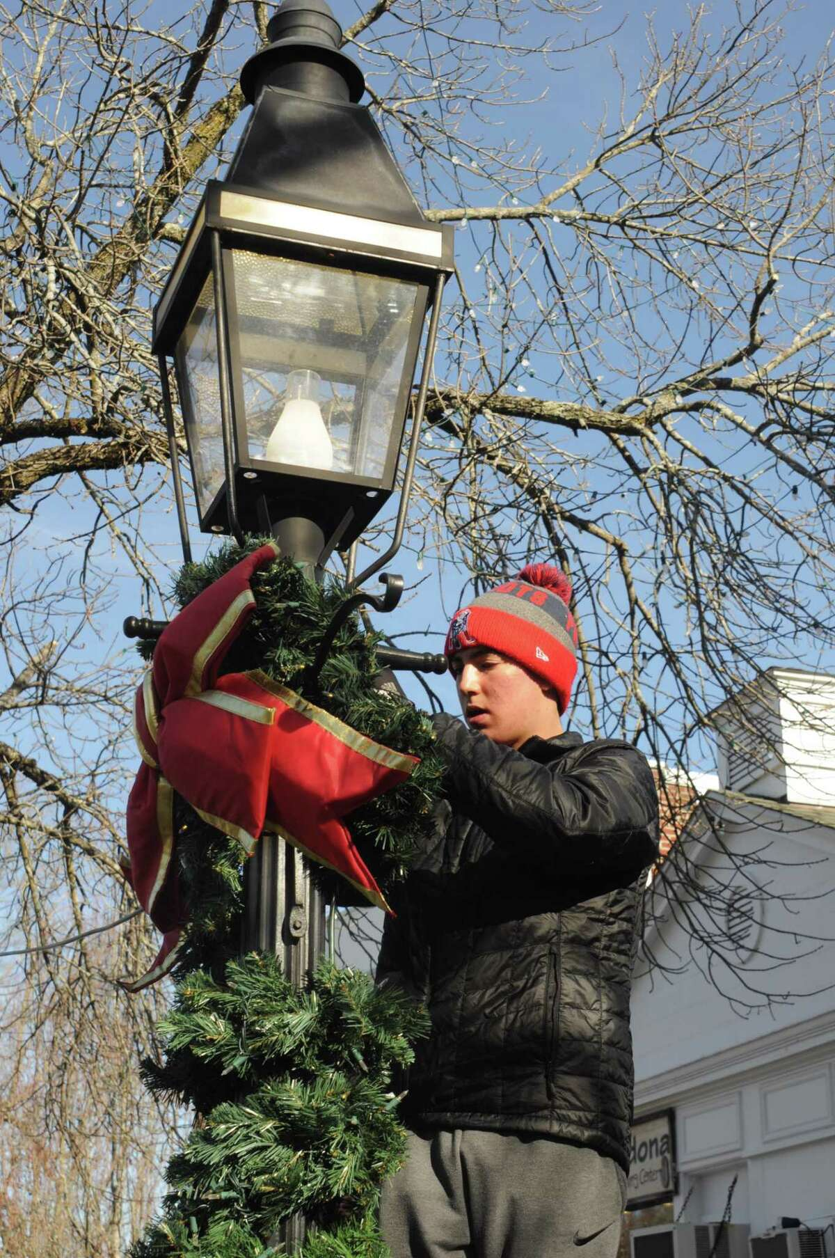 Will Hanna was one of the players from the American Legion baseball team out decorating village lampposts Saturday, Nov. 23, in a joint effort with veterans from American Legion Post 78.