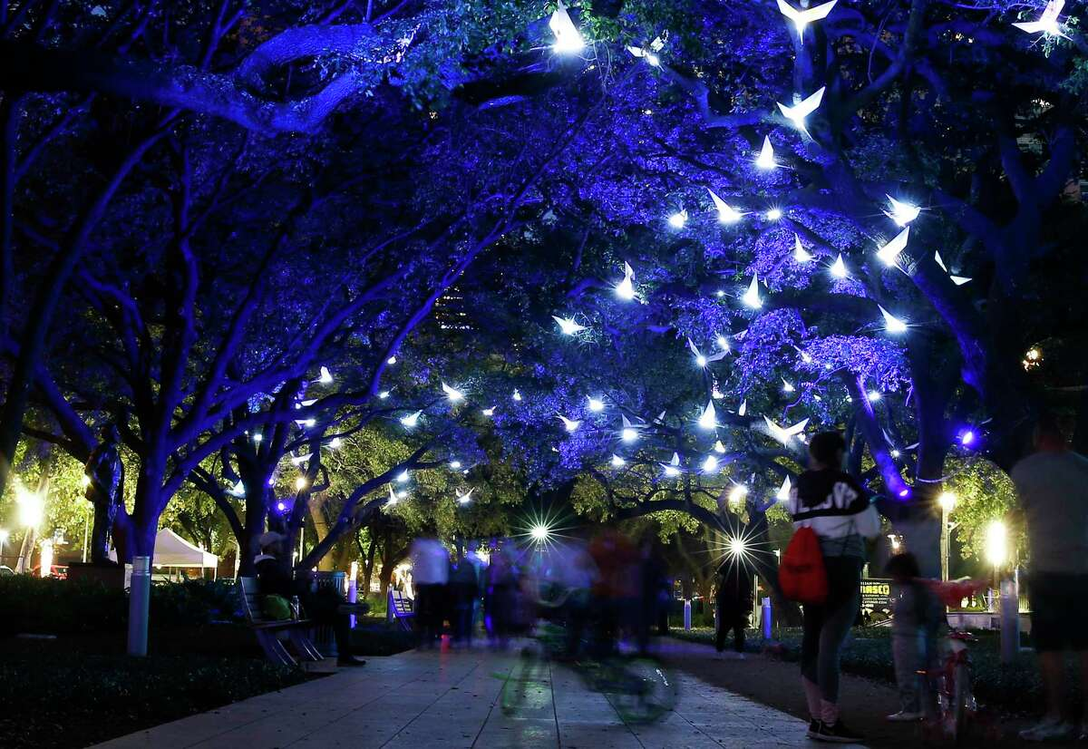 People walk under Discovery Green's holiday exhibit