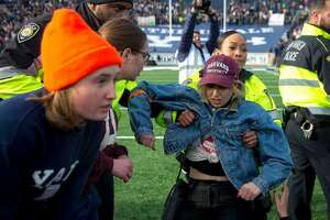 A student is detained during a protest at the Yale-Harvard game at Yale Bowl, New Haven. Conn. on Nov. 23, 2019.