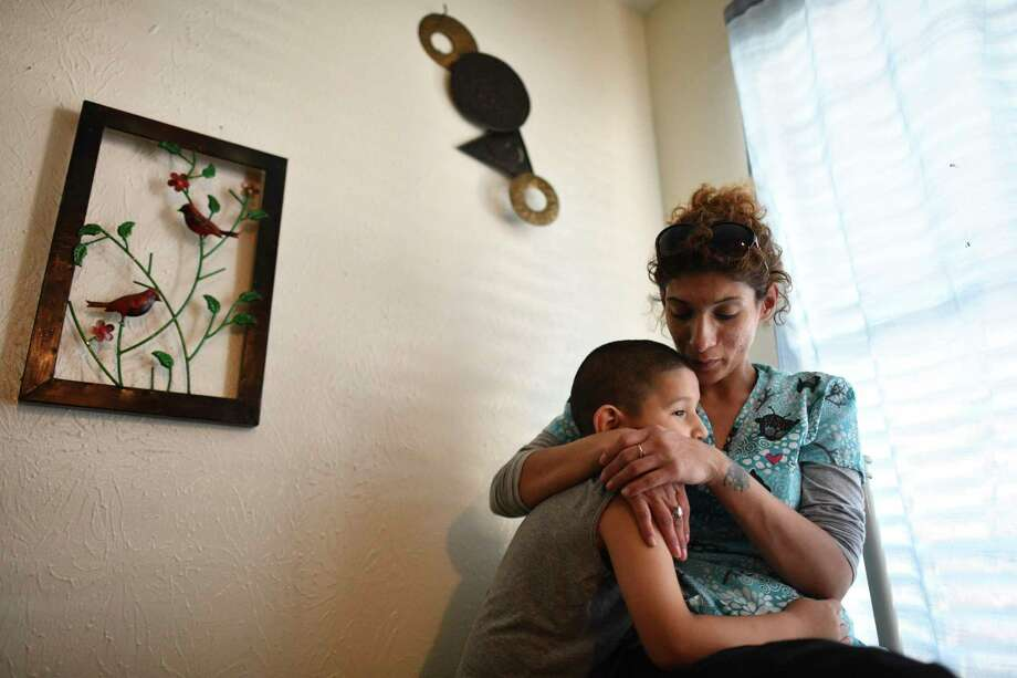 Rebecca Perez holds her son Leroy Gomez, now 7, in their apartment before they were evicted. She and her two boys now live with her father. Photo: Billy Calzada / San Antonio Express-News