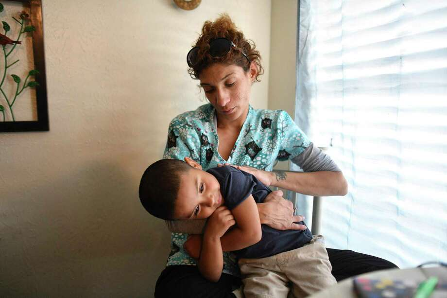 After losing one of her jobs and falling behind three months in her rent, single mother Rebecca Perez was evicted from her apartment. Perez, holding her son Noah Gomez, 4, paid more than half her income on rent, well above what's considered affordable. Photo: Billy Calzada / San Antonio Express-News
