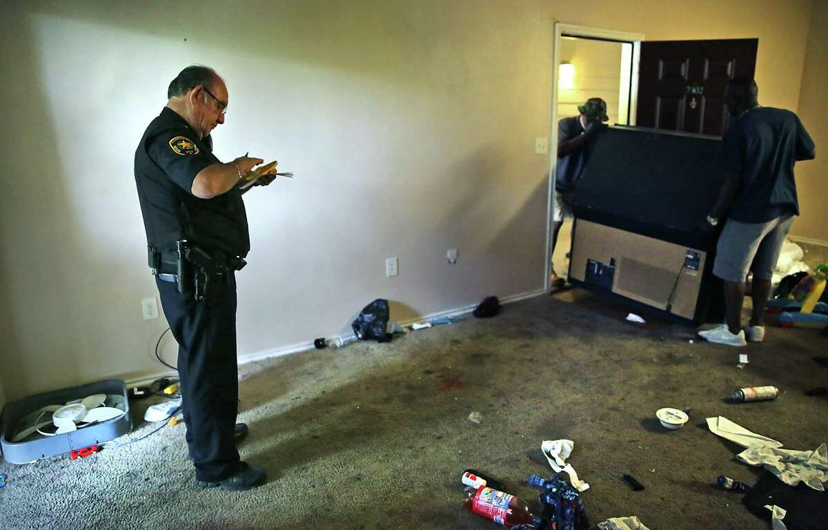 Deputy Constable Rudy Castillo of Precinct 4 stands by as a crew removes belongings left behind by a family.