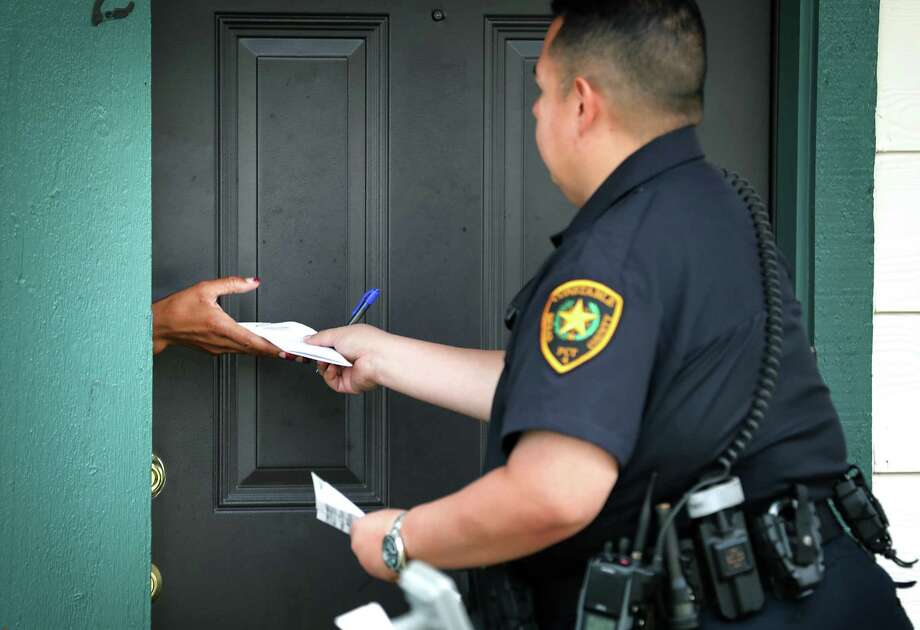 Bexar County Deputy Constable Edward Prado of Precinct 4 served this eviction citation last year to an apartment tenant. Photo: Bob Owen /San Antonio Express-News / San Antonio Express-News