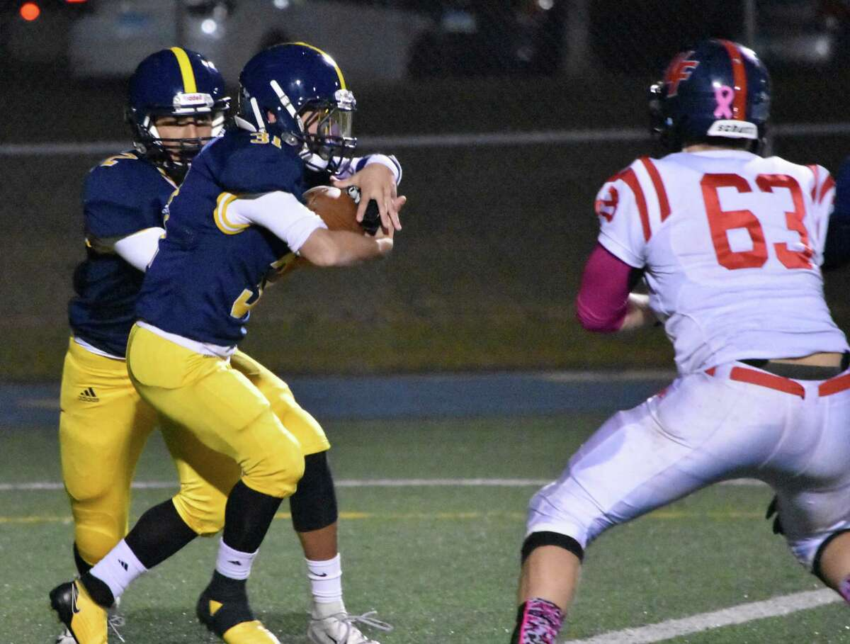 East Haven's Trey Garea hands the ball of to Eric Araujo in the football game between East Haven and New Fairfield at East Haven high on Oct. 18, 2019. (Pete Paguaga, Hearst Connecticut Media)