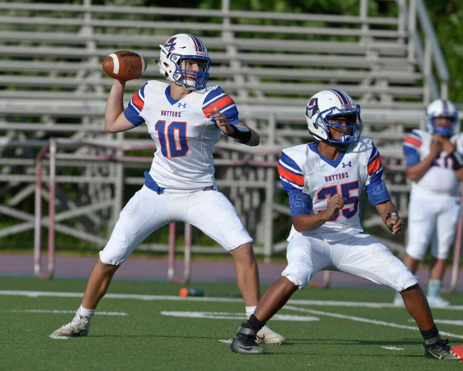Quarterback Patrick Rosetti (10 White) sets to throw a pass behind protection from Khuron Na (35 White) in the Danbury High School Hatters Blue & White spring football game. Friday, June 14, 2019, at Danbury High School, Danbury. Photo: H John Voorhees III / Hearst Connecticut Media / The News-Times