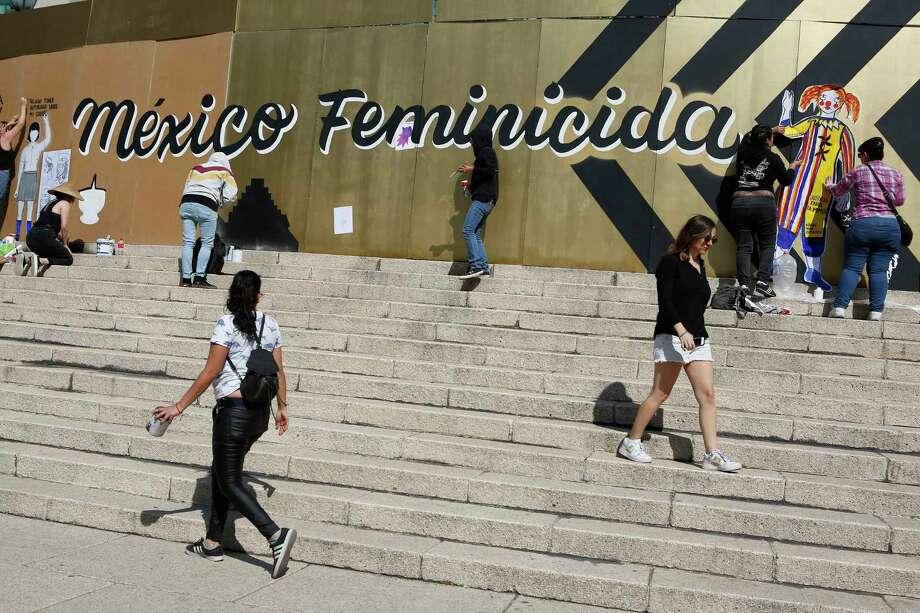 Grupos de mujeres opuestas a la violencia de género pintan consignas en las tablas que rodean el monumento del Ángel de la Independencia en la Ciudad de México, el domingo 24 de noviembre de 2019. Photo: Ginnette Riquelme /Associated Press / Copyright 2019 The Associated Press. All rights reserved.