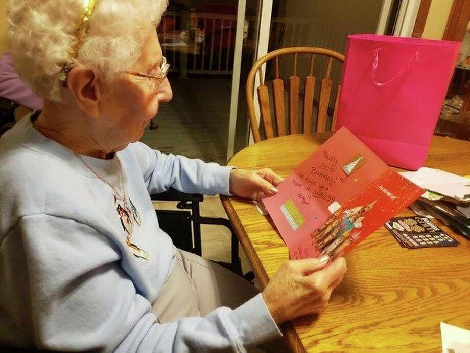 Janet Sadowsky reads a birthday card, one ofmany sent to honor her milestone birthday. (Courtesy photo)