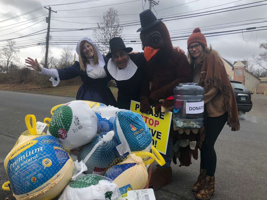 Dr. Bruce Sofferman, owner of Smile Dental Center, his wife, Deborah, left, and daughter Sophia, right, along with quite an enthusiastic turkey collected donations for Spooner House on Wednesday outside his office's location at 1000 Bridgeport Avenue. Photo: Brian Gioiele / Hearst Connecticut Media / Connecticut Post