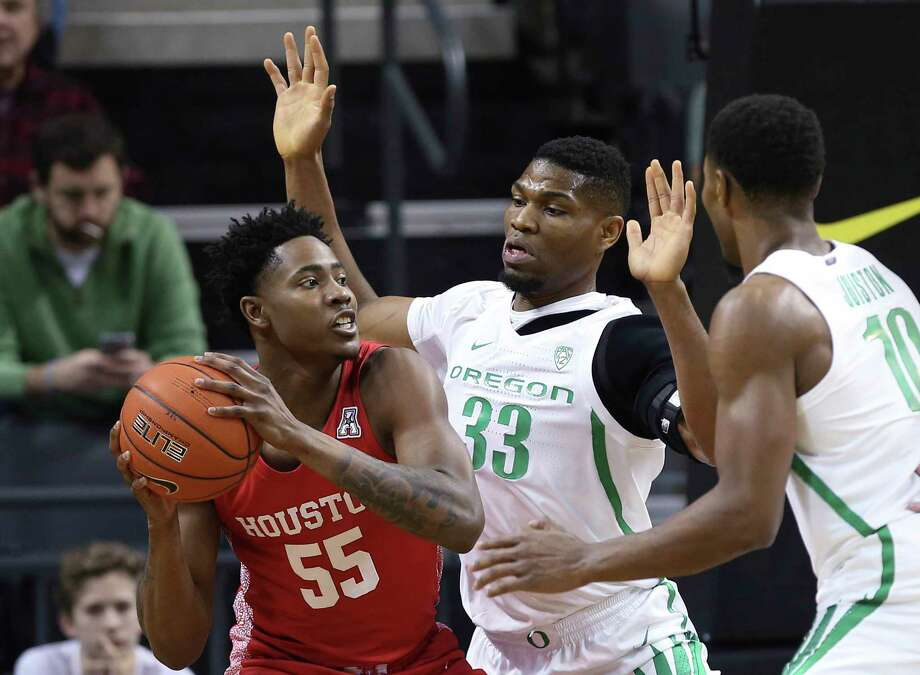Houston's Brison Gresham, left, looks for a teammate under pressure from Oregon's Francis Okoro, center, and Shakur Juiston during the first half of an NCAA college basketball game in Eugene, Ore., Friday, Nov. 22, 2019. (AP Photo/Chris Pietsch) Photo: Chris Pietsch, Associated Press / Copyright 2019 The Associated Press. All rights reserved.