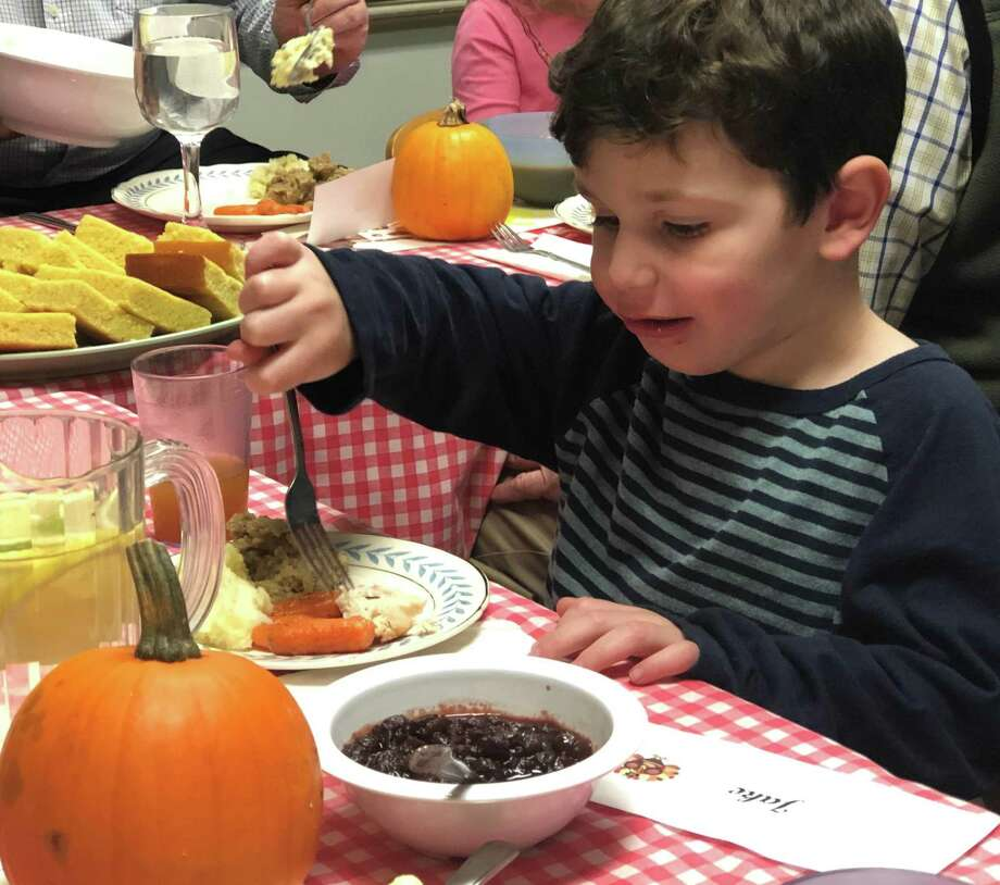Jake Hangac, 4, digs into his Thanksgiving meal during the festivities. Photo: Deborah Rose / Hearst Connecticut Media / The News-Times  / Spectrum