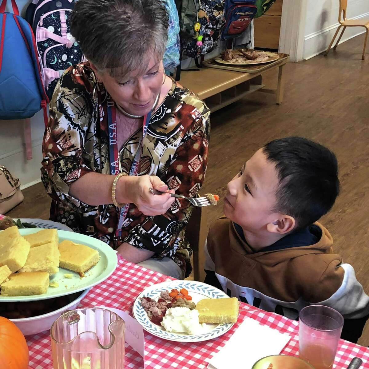 Diane Cunningham of the personnel office at Roger Sherman Town Hall in New Milford, encourages Carlson Cai, 4, to eat his vegetables during the meal.