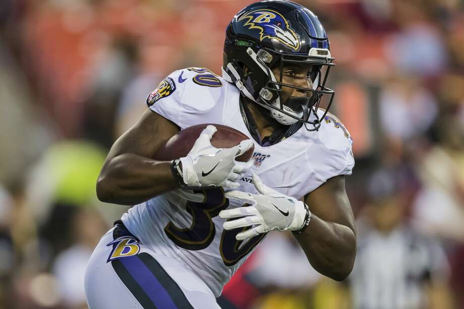 PHOTOS: Texans vs. Colts LANDOVER, MD - AUGUST 29: Kenneth Dixon #30 of the Baltimore Ravens carries the ball during the first half of a preseason game against the Washington Redskins at FedExField on August 29, 2019 in Landover, Maryland. (Photo by Scott Taetsch/Getty Images) >>>See more photos from the Texans' win Thursday ... Photo: Scott Taetsch/Getty Images