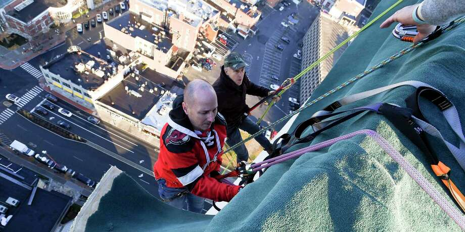 Brian Cashman, left, General Manager of the New York Yankees, and Brian Van Orsdel make a practice rappel off Stamford's Landmark Building in 2017. The annual event returns December 8 at 5 p.m. Photo: Matthew Brown / Hearst Connecticut Media File Photo / Stamford Advocate