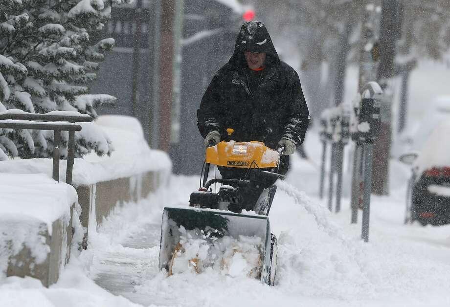 A man clears a Denver sidewalk after a storm packing snow and high winds hit the region. The storm is headed toward South Dakota, Iowa, Michigan, Minnesota and Wisconsin Photo: David Zalubowski / Associated Press