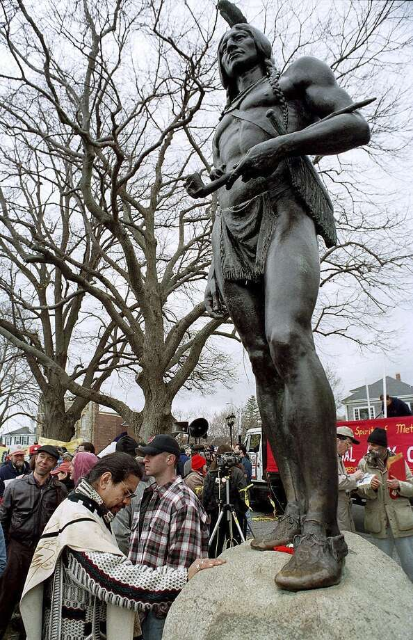FILE - In this Nov. 26, 1998, file photo, Andres Araica, of Boston, prays in front of a statue of Massasoit in Plymouth, Mass., before a protest march to commemorate the annual National Day of Mourning on Thanksgiving Day. United American Indians of New England held the first National Day of Mourning in 1970, and again plan to gather at noon on Thanksgiving Day, Thursday, Nov. 28, 2019. (AP Photo/Neal Hamberg, File) Photo: Neal Hamberg, Associated Press