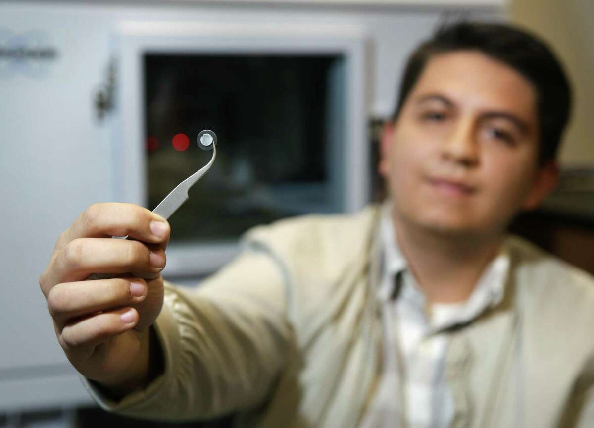 UTSA graduate student Joel Gomez holds a human bone sample in front of the machine that scans and analyzes its make-up.