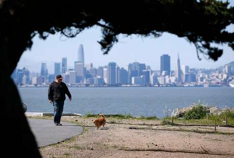 John Garrett and Romeo stroll along a bayside trail at Point Isabel Regional Shoreline in Richmond, Calif. on Friday, April 12, 2019. Bay Area temperatures are expected to rise into the 70's over the weekend.