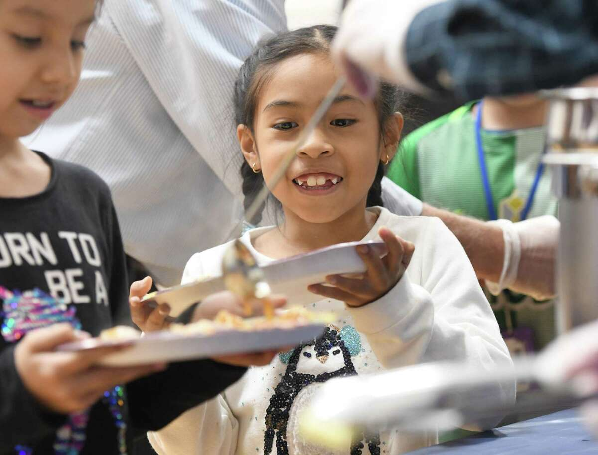 Leah Javier, 7, waits to be served dinner at the annual Thanksgiving Feast for Members at the Boy & Girls Club in Greenwich, Conn. Tuesday, Nov. 26, 2019. Volunteers and staff were on hand to provide dinner with all the Thanksgiving fixings to club members.