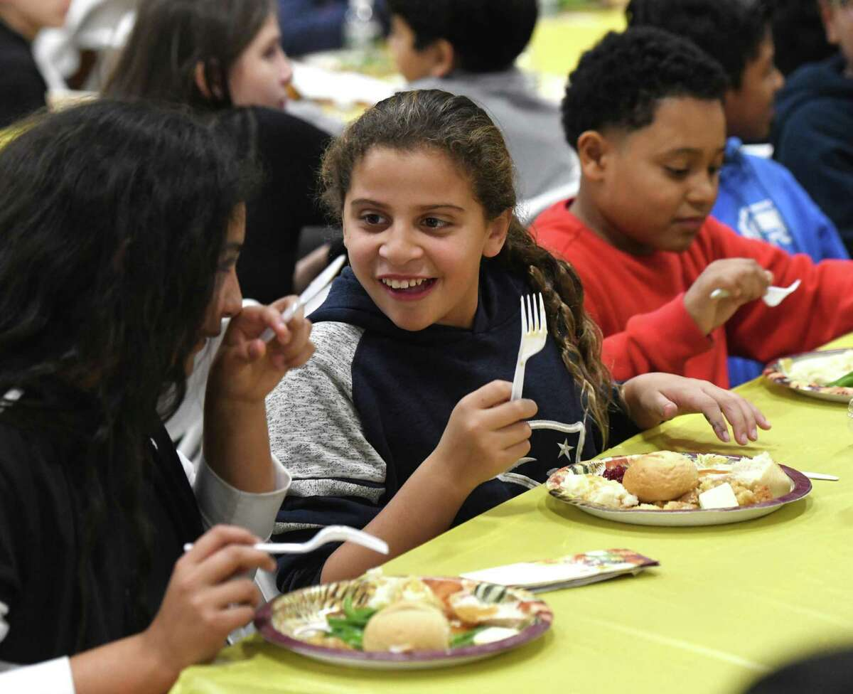 Ashley Mariscal, 11, eats with friends at the annual Thanksgiving Feast for Members at the Boy & Girls Club in Greenwich, Conn. Tuesday, Nov. 26, 2019. Volunteers and staff were on hand to provide dinner with all the Thanksgiving fixings to club members.