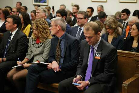Tim Eyman, front right, uses his phone during a hearing where a coalition of counties, transportation agencies and the city of Seattle argued in front of a King County Superior Court judge for a motion to block Eyman's Initiative 976 from taking effect Dec. 5, saying there would be irreparable harm, that it was unconstitutional and violated the single-subject rule, Tuesday, Nov. 26, 2019. Photo: Genna Martin, Seattlepi.com / GENNA MARTIN