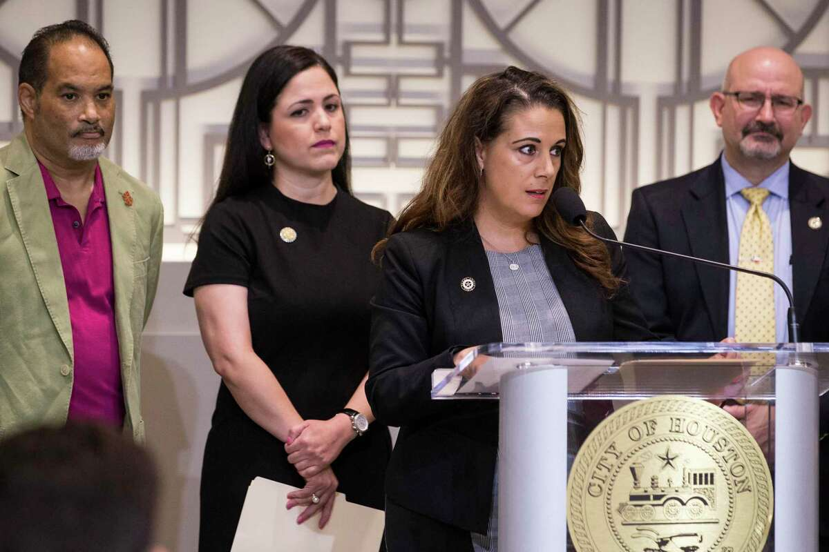 Rep. Gina Calanni, at the podium, and Rep. Jon Rosenthal, far right, stand with other members of the Texas House Democratic Caucus, during a news conference to demand Gov. Greg Abbott to call a special session aimed at limiting gun violence on Wednesday, Sept. 4, 2019, in Houston.