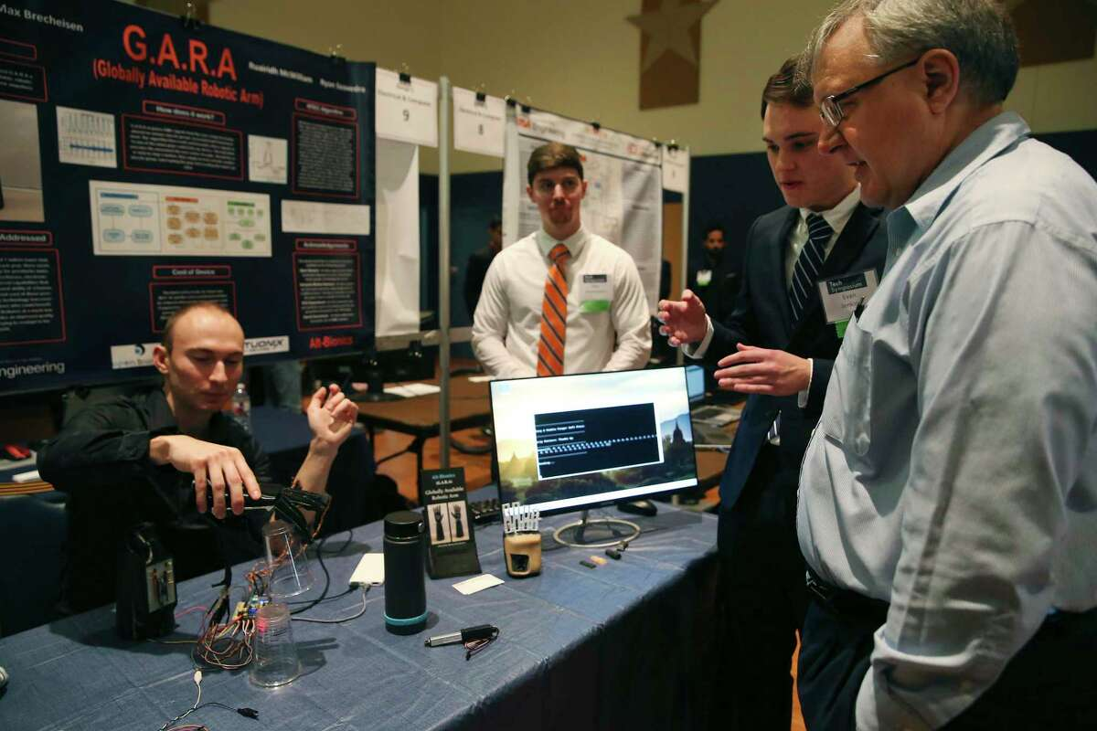 Electrical and computer engineering professor Lars Hansen, right, listens as, from left, Ryan Saavedra, Max Brecheisen and Evan Jenkins explain their Globally Available Robotic Arm at the University of Texas at San Antonio Fall 2019 Tech Symposium on Tuesday. They and fellow student Ruairidh McWilliam designed and built the low-cost bionic hand for below-elbow amputees.