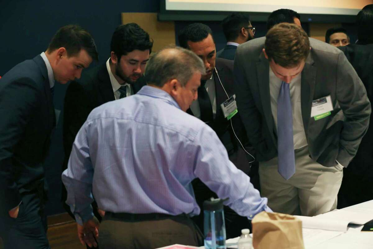 Civil engineering undergraduate students, from left, Conner Murphy, 22, and Tyler Surles, 22, both from Houston, Alexander Manjarres, 27, of San Antonio and Kyler Felux, 23, of Poth, listen as alumnus Damien Herrera offers advice during the University of Texas at San Antonio Fall 2019 Tech Symposium on Tuesday. The team designed construction of a restaurant site.