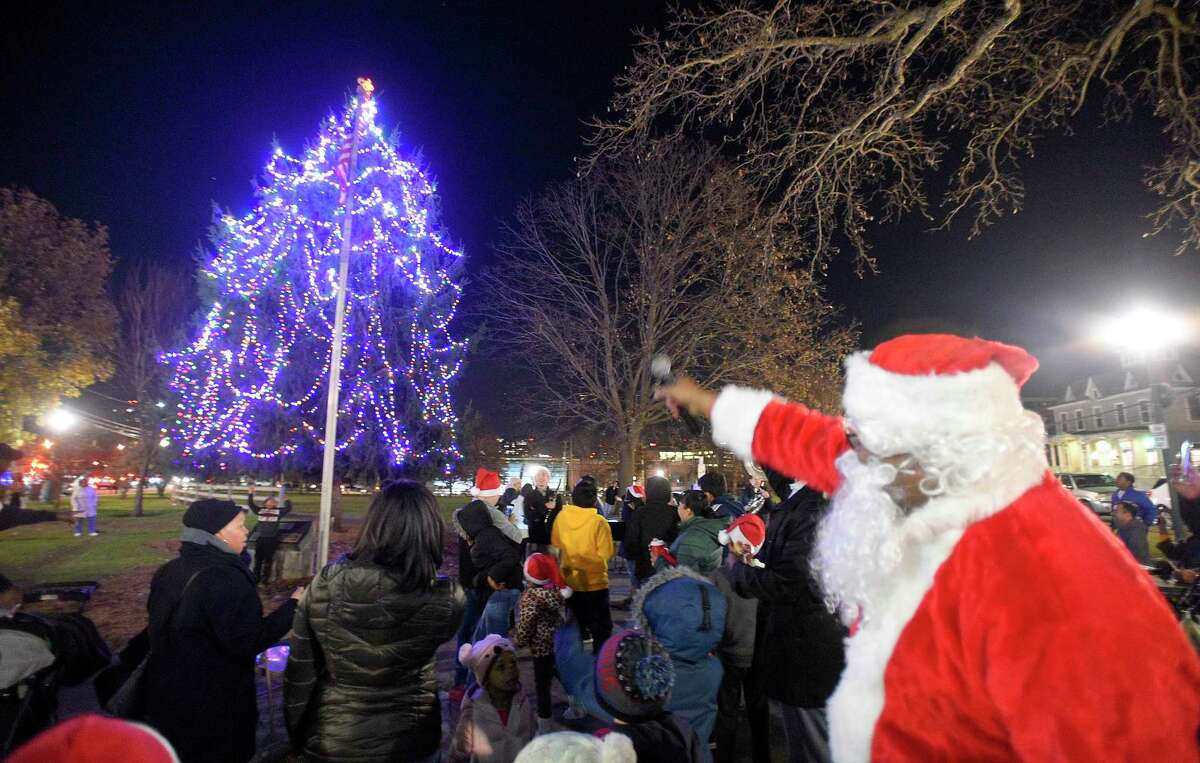 Santa Claus (Stamford resident Thomas Patterson) points and magically the lights sparkle as the tree lights up to the joys and cheers of children and families attending the Jackie Robinson Park of Fame's 25th Annual Christmas Tree Lighting on Nov. 26, 2019 in Stamford, Connecticut. Several West side residents, community leaders enjoy the holiday festivity that included musical selections performed by children of Project Music, holiday treats and hot chocolate and a visit by Santa Claus.