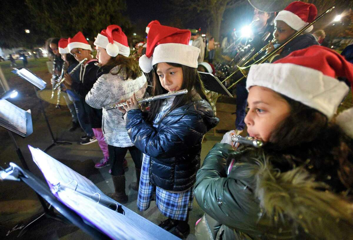 Nathaly Barreto, center, and Ailyn Martinez, at right, along with several other performers of Project Music, play a musical holiday selection