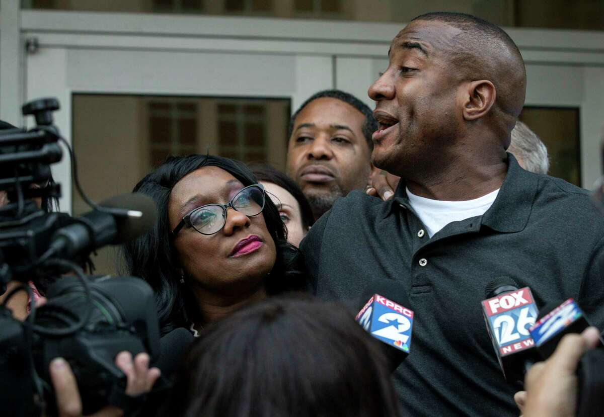 Donna Poe looks off as her son Lydell Grant talks to reporters after being released on bond on Tuesday, Nov. 26, 2019, in Houston. Earlier in the day, a judge ordered Grant released after prosecutors and defense attorneys with the Innocence Project of Texas agreed that Grant should be freed while the case is investigated further in light of new DNA evidence. Grant was convicted of murder in the 2010 stabbing death of Aaron Scheerhoorn outside of a Montrose bar, and he had spent seven years behind bars.