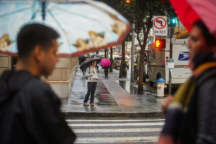 People wait to cross Sutter and Montgomery streets under umbrellas during a rainstorm in the Financial District in San Francisco, California, on Tuesday, Nov. 26, 2019. Photo: Gabrielle Lurie, The Chronicle