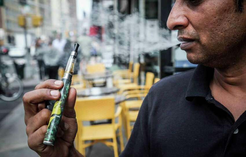 FILE - In this Sept. 16, 2019 file photo, Inam Rehman, manager of Jubilee Vape & Smoke Inc., vapes in New York. City lawmakers are poised to enact a ban on flavored e-cigarettes Tuesday, Nov. 26, 2019. (AP Photo/Bebeto Matthews, File)