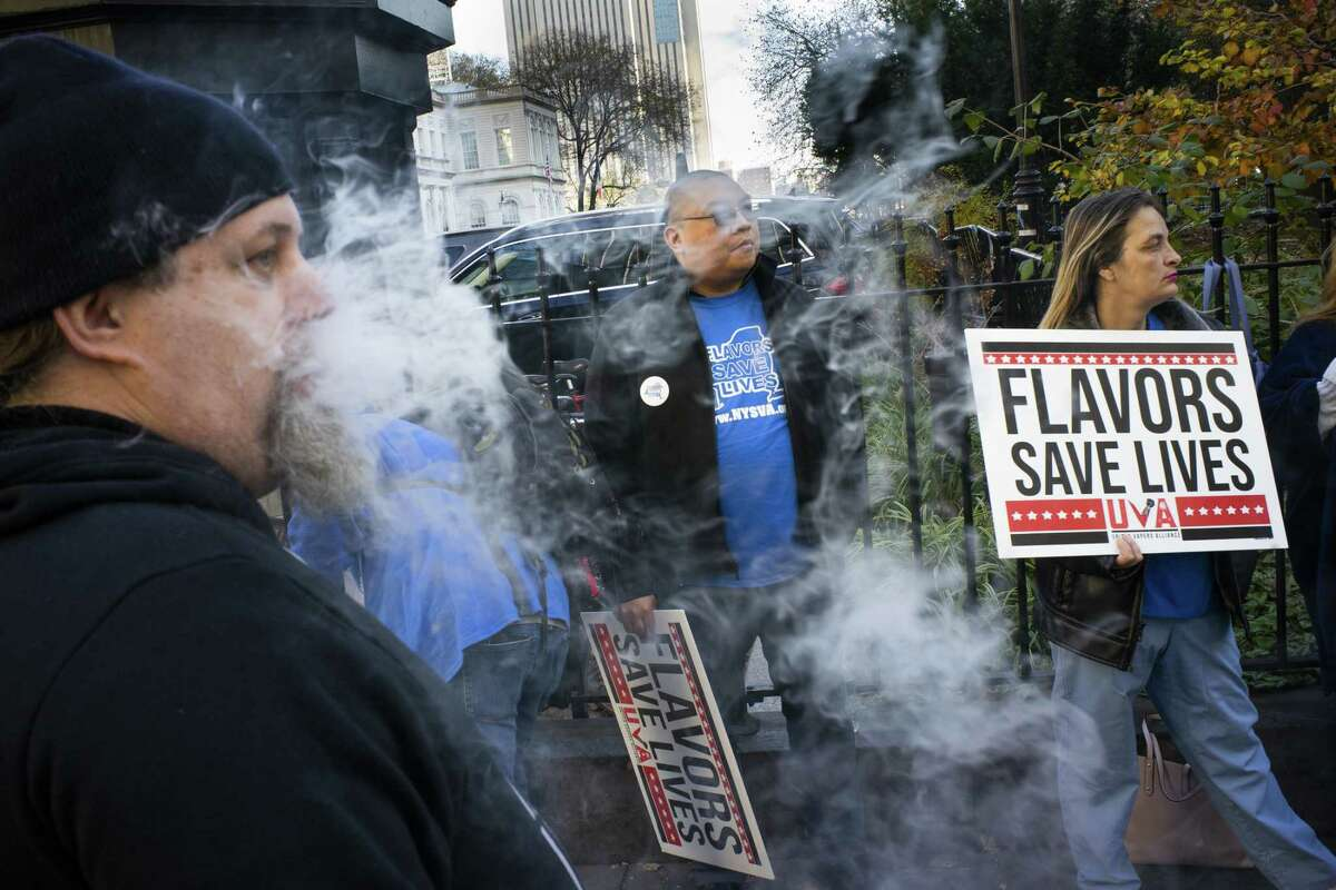 NEW YORK, NY - NOVEMBER 26: People hold banners as they protest against the New York City Council vote on legislation to ban flavored e-cigarettes outside City Hall on November 26, 2019 in New York City. New York is voting to be the first big city to ban flavored e-cigarettes and comes days after New Yorks's second vaping death. (Photo by Eduardo Munoz Alvarez/Getty Images)