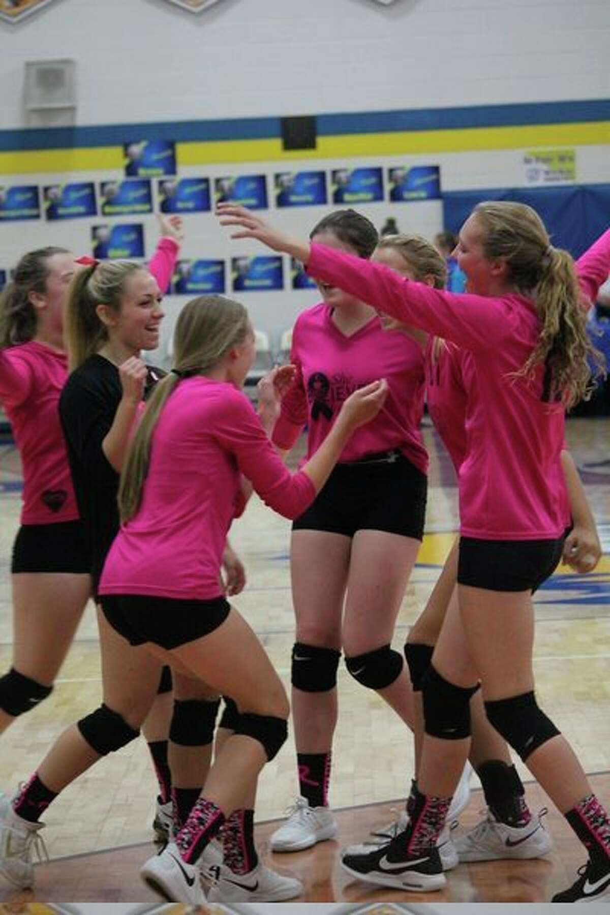 Evart volleyball players celebrate a point during the regular season. (Herald Review file photo)
