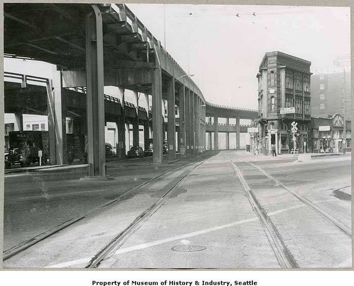 Alaskan Way Viaduct from 1st Ave., Seattle, 1960 The Alaskan Way Viaduct was an elevated highway in Seattle which opened in 1966 after 16 years of construction and decades of planning. The double-decked highway runs along the Elliott Bay waterfront above the surface street, Alaskan Way, following previously existing railroad lines. The viaduct provided Seattle with its first bypass route around the downtown business district, relieving traffic congestion. The viaduct was damaged in the 2001 Nisqually earthquake. This image was taken facing northwest and looking from street level up to the viaduct at the intersection of Railroad Avenue, First Avenue, and Dearborn Street, in the Pioneer Square neighborhood The wedge-shaped building on the right, the Flatiron Building, still stands as of 2019.