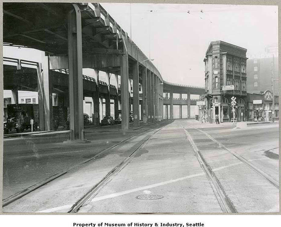 Alaskan Way Viaduct from 1st Ave., Seattle, 1960  The Alaskan Way Viaduct was an elevated highway in Seattle which opened in 1966 after 16 years of construction and decades of planning. The double-decked highway runs along the Elliott Bay waterfront above the surface street, Alaskan Way, following previously existing railroad lines. The viaduct provided Seattle with its first bypass route around the downtown business district, relieving traffic congestion. The viaduct was damaged in the 2001 Nisqually earthquake.  This image was taken facing northwest and looking from street level up to the viaduct at the intersection of Railroad Avenue, First Avenue, and Dearborn Street, in the Pioneer Square neighborhood  The wedge-shaped building on the right, the Flatiron Building, still stands as of 2019. Photo: MOHAI Seattle Historical Society Collection [SHS3978], Courtesy Of MOHAI / Courtesy of MOHAI