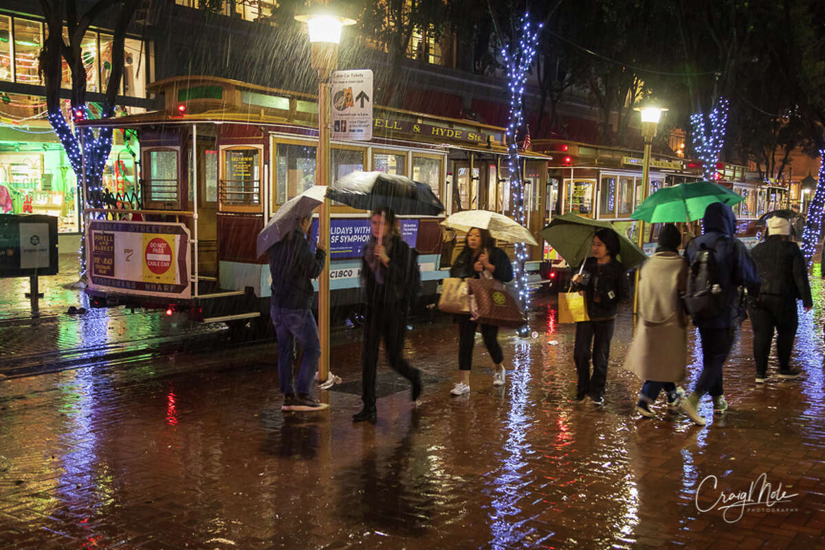 Pedestrians in San Francisco cover from the rainstorm that swept the region on Tuesday night, Nov. 26, 2019.