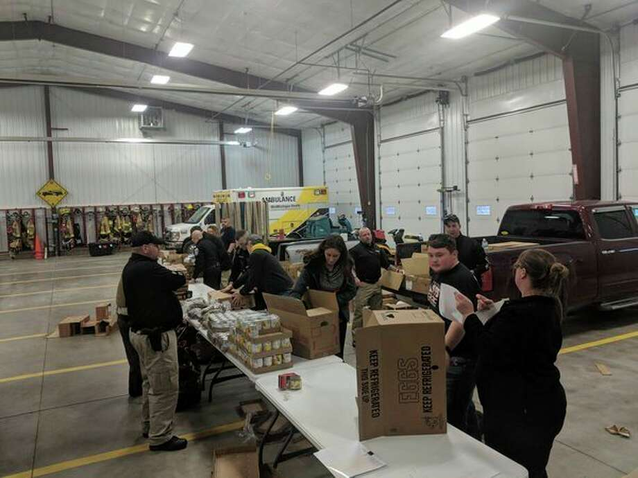 Gladwin County law enforcement officers along with Beaverton High School students pack up Thanksgiving dinners for 90 families serving more than 400 people at the Beaverton Fire Department on Tuesday. (Photo by Tereasa Nims for the Daily News)
