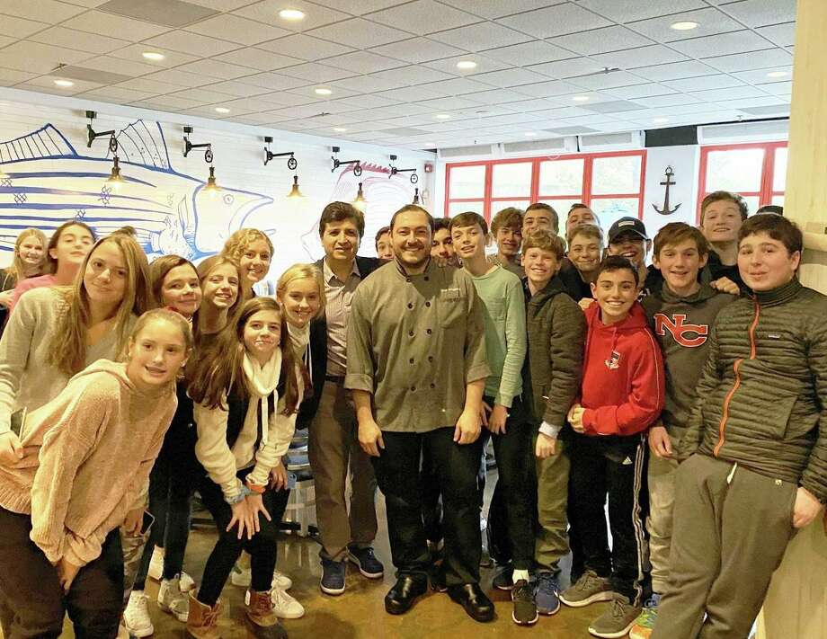 Saxe Middle School 8th grade Spanish students at New Canaan's Pesca restaurant with owners Wilson Rodriguez and José Draganac during a recent school field trip. Photo: Contributed Photo