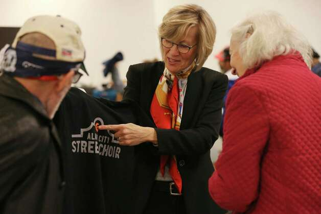 The Alamo City Street Choir Director Tracy Bjella Powers, center, shows off donated tee shirts as the group prepares to perform during Sunday Service at Travis Park Methodist Church, Nov. 24, 2019. The choir is made up of homeless people. Photo: Jerry Lara, San Antonio Express-News / Staff Photographer / **MANDATORY CREDIT FOR PHOTOG AND SAN ANTONIO EXPRESS-NEWS/NO SALES/MAGS OUT/TV   © 2019 San Antonio Express-News