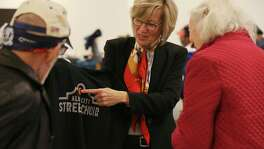 The Alamo City Street Choir Director Tracy Bjella Powers, center, shows off donated tee shirts as the group prepares to perform during Sunday Service at Travis Park Methodist Church, Nov. 24, 2019. The choir is made up of homeless people.