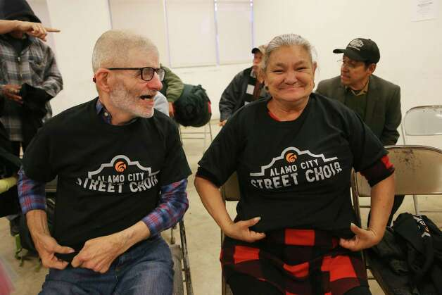 Carl Woods, 56, and Angie Salazar, 55, try on Alamo City Street Choir tee shirts before their performance during Sunday Service at Travis Park Methodist Church, Nov. 24, 2019. The choir is made up of homeless people. The tee shirts were donated along with the logo design. Photo: Jerry Lara, San Antonio Express-News / Staff Photographer / **MANDATORY CREDIT FOR PHOTOG AND SAN ANTONIO EXPRESS-NEWS/NO SALES/MAGS OUT/TV   © 2019 San Antonio Express-News