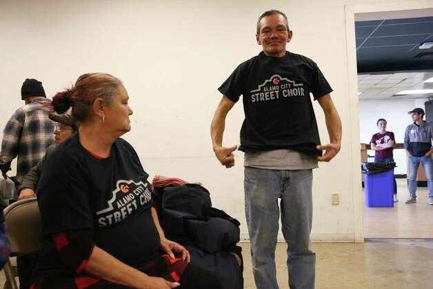 Guadalupe Caballero, 45, right, tries on an Alamo City Street Choir T-shirt as Angie Salazar, 55, watches, Sunday, Nov. 24, 2019. The choir, made up of homeless people, performed during Sunday Service at Travis Park Methodist Church. Photo: Jerry Lara /Staff Photographer / **MANDATORY CREDIT FOR PHOTOG AND SAN ANTONIO EXPRESS-NEWS/NO SALES/MAGS OUT/TV   © 2019 San Antonio Express-News