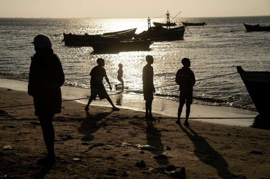 Kids play on the shore as fishermen come in on boats, most organized by family, to give the women their catches for the day to clean and sell at the artisanal fish market beach in Tombwa, Angola on May 16, 2019. Photo: Washington Post Photo By Carolyn Van Houten. / The Washington Post